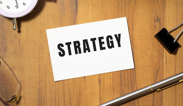 Eine visitenkarte mit dem text strategie liegt auf einem hölzernen bürotisch zwischen büromaterial. unternehmenskonzept.