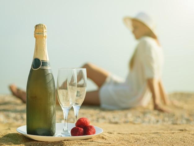 Eine volle flasche schamanen, erdbeeren und die frau am strand.