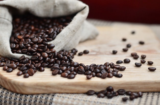 Eine volle tüte braune kaffeebohnen liegt auf einer holzoberfläche