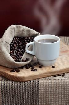 Eine volle tüte braune kaffeebohnen und eine weiße tasse heißen kaffee liegt auf einer holzoberfläche
