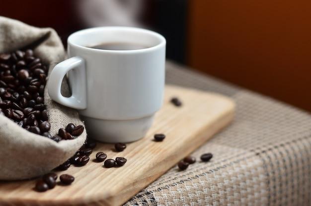 Eine volle tüte braune kaffeebohnen und eine weiße tasse heißen kaffee