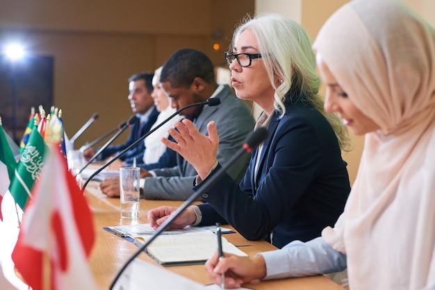 Eine von selbstbewussten delegierten oder politikern in abendgarderobe, die ausländischen kollegen die hauptidee ihrer rede erklärte