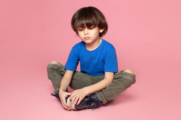 Eine vorderansicht betonte jungen im blauen t-shirt und in der khakihose auf dem rosa raum