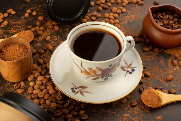 Eine vorderansicht braune kaffeesamen mit schokoriegeln und einer tasse kaffee überall auf der braunen oberfläche kaffeesamenkorngranulat