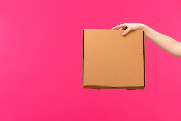 Eine vorderansicht braune kastenhand, die braune kastenweibchenhand-rosa hintergrundfarbnahrungsmittelpaket hält