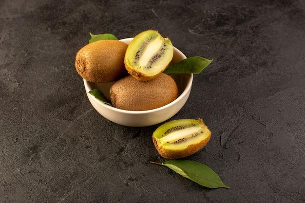 Eine vorderansicht braune kiwis frische reife isolierte saftige weiche ganze und geschnittene früchte zusammen mit grünen blättern innerhalb der weißen platte auf dem dunklen hintergrund exotische frucht frisch
