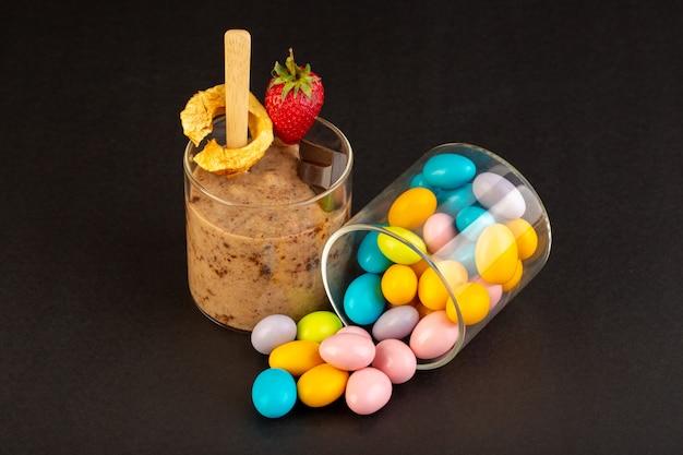 Eine vorderansicht braune schoko-dessert lecker lecker süß mit kaffee-schokoriegel und erdbeere mit süßigkeiten auf dem dunklen hintergrund süße erfrischung dessert