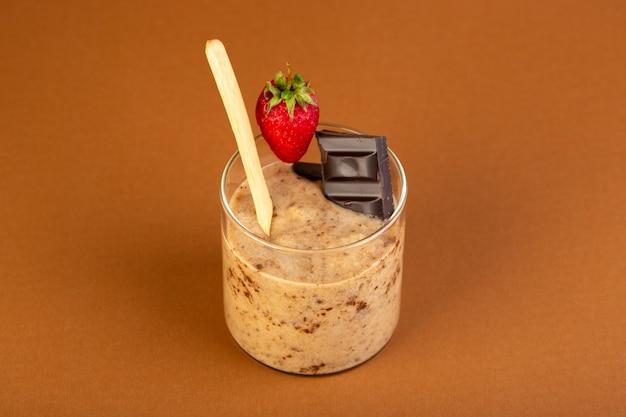 Eine vorderansicht braune schoko-dessert lecker lecker süß mit pulverisiertem kaffee schokoriegel und erdbeere isoliert auf dem milchkaffee hintergrund süßes erfrischungsdessert
