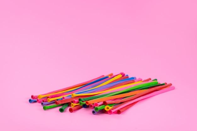 Eine vorderansicht bunte stockstrohhalme lang auf rosa, farbigem regenbogenfoto