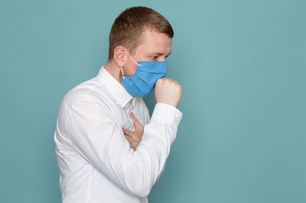 Eine vorderansicht, die jungen mann im weißen hemd mit blauer maske auf dem blauen raum hustet