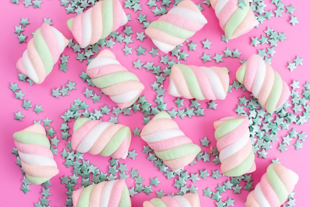 Eine vorderansicht, die marshmallows kaut, alles auf rosa, mit sternförmigen bonbonpartikeln, die regenbogenzuckerkonfiguration färben