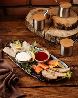 Eine vorderansicht fleisch und fisch mit verschiedenen saucen auf dem holztisch essen mahlzeit fleisch