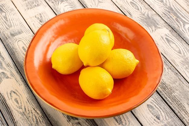 Eine vorderansicht frische zitronen sauer reife milde saftige zitrusfrüchte in orange platte vitamin gelb auf dem grauen rustikalen schreibtisch