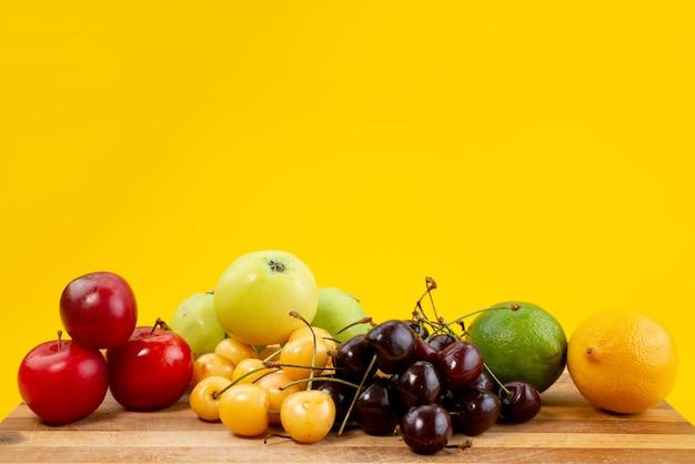 Eine vorderansicht fruchtzusammensetzung weich und saftig auf gelber, fruchtsommerfarbe