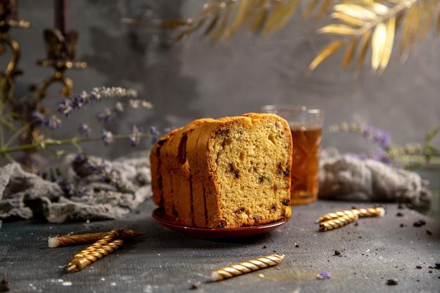 Eine vorderansicht gebackenen kuchen mit kerzen lila blumen und tee auf dem grauen schreibtisch