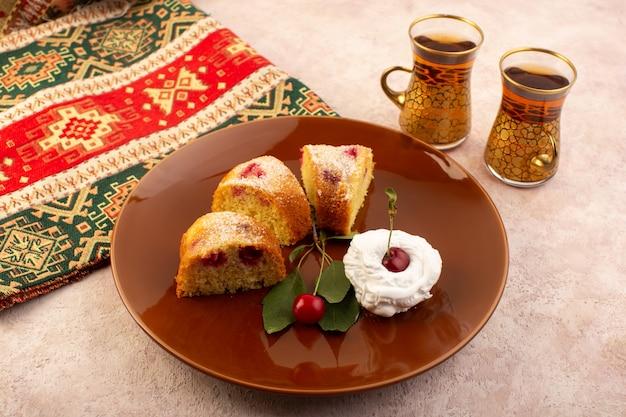 Eine vorderansicht gebackenen obstkuchen köstlich geschnitten mit roten kirschen innen und zuckerpulver innen runde braune platte auf rosa