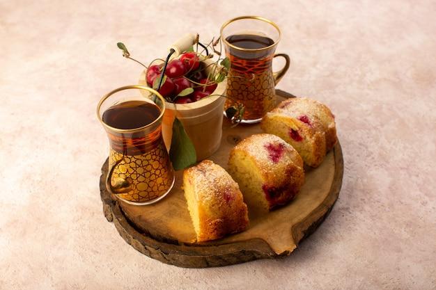 Eine vorderansicht gebackener obstkuchen köstlich geschnitten mit roten kirschen innen und zuckerpulver auf holzschreibtisch mit frischem kirschentee auf rosa