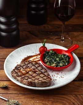 Eine vorderansicht gebratenes fleisch mit soße und gemüse zusammen mit einem glas wein auf dem braunen schreibtisch essen fleisch mahlzeit