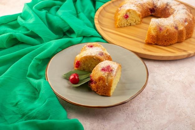 Eine vorderansicht kirschkuchen schneidet köstlich und lecker auf dem rosa schreibtisch