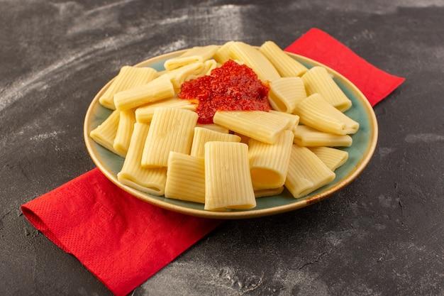 Eine vorderansicht kochte italienische nudeln mit tomatensauce innerhalb platte auf dem grauen tischnudeln italienisches essen mahlzeit