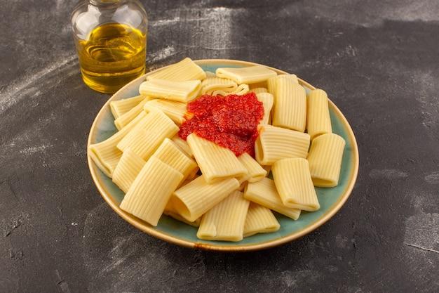 Eine vorderansicht kochte italienische nudeln mit tomatensauce innerhalb platte auf der grauen oberfläche