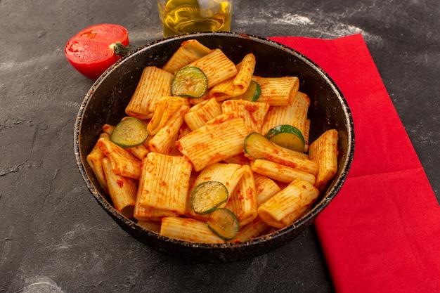 Eine vorderansicht kochte italienische nudeln mit tomatensauce und gurke in der pfanne auf dem dunklen schreibtisch