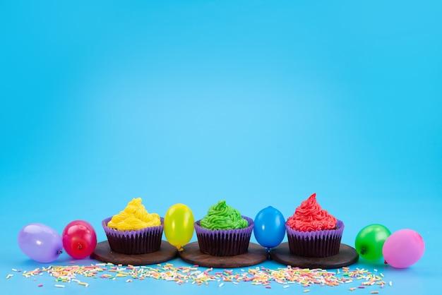 Eine vorderansicht köstliche brownies-schokolade, die zusammen mit bonbons und kugeln auf blauer, bonbonkuchen-keksfarbe basiert