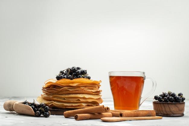 Eine vorderansicht köstliche runde pfannkuchen lecker und rund geformt mit blaubeeren und zimtpfannkuchengebäck, das zucker kocht
