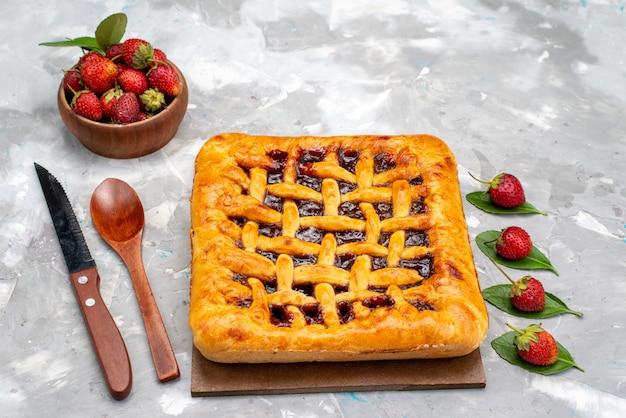 Eine vorderansicht köstlichen erdbeerkuchen mit erdbeergelee nach innen zusammen mit frischen erdbeeren auf dem grauen schreibtischkuchen