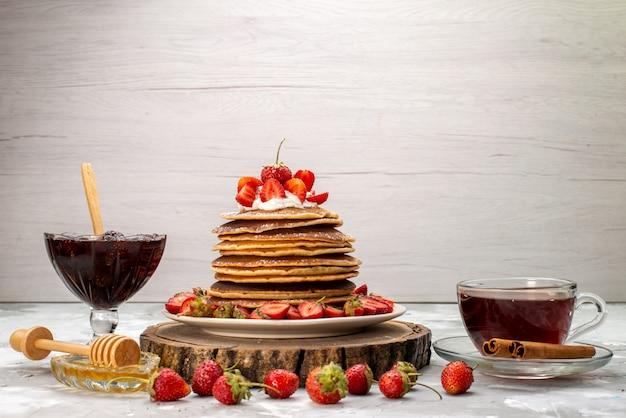 Eine vorderansicht leckere runde pfannkuchen mit sahne-tee und roten erdbeeren auf dem hölzernen schreibtischkuchen