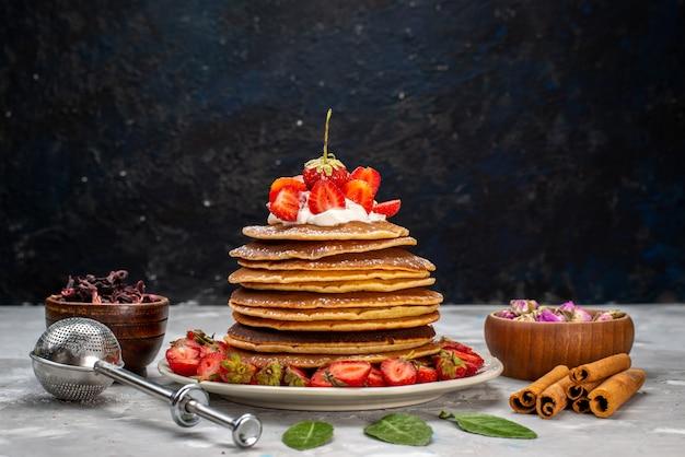 Eine vorderansicht leckere runde pfannkuchen mit sahne und roten erdbeeren auf dem leichten schreibtischkuchen