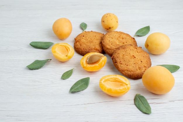 Eine vorderansicht orange aprikosen ganz und gewürzt mit grünen blättern und keksen auf dem hellen schreibtisch