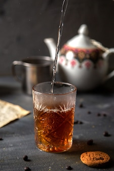 Eine vorderansicht-person, die tee mit gekochtem wasser zusammen mit keksen auf dem dunklen tischkeks-tee-kekszucker süß macht