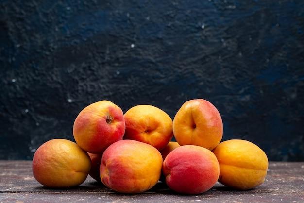 Eine vorderansicht pfirsichfarben und saftig auf dem hölzernen schreibtischfruchtsommerfoto-fruchtfleisch