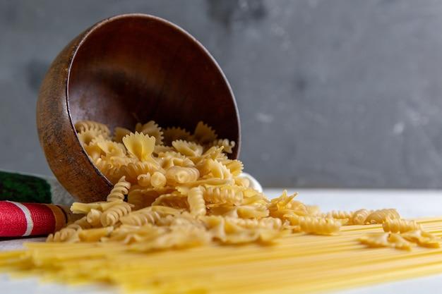 Eine vorderansicht rohe italienische nudel lange und kleine nudelschale