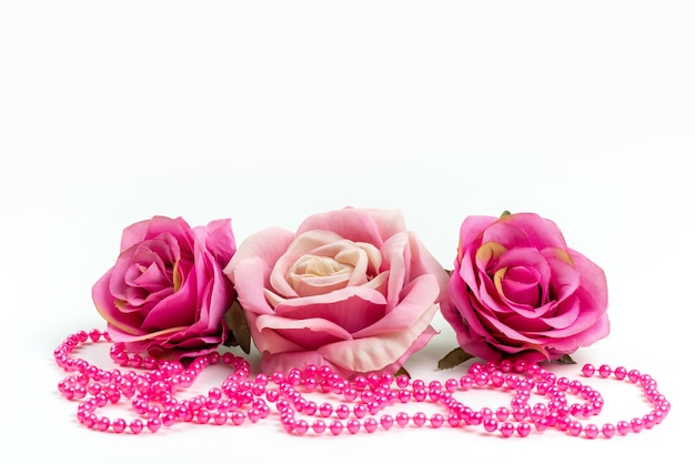Eine vorderansicht rosa rosen zusammen mit rosa halskette auf weißem schreibtisch