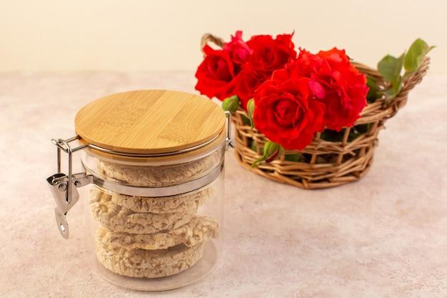 Eine vorderansicht rote rosen schöne rosa und rote blumen im korb zusammen mit chips auf rosa isoliert