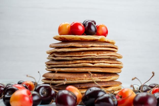 Eine vorderansicht runde pfannkuchen gebacken und lecker mit kirschen auf dem leichten schreibtisch kuchen obst