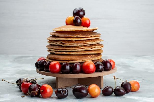 Eine vorderansicht runde pfannkuchen mit kirschen auf der hellen schreibtischkuchenfrucht