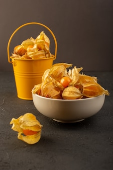 Eine vorderansicht schälte orange früchte innerhalb der weißen platte und des gelben korbs lokalisiert auf grau