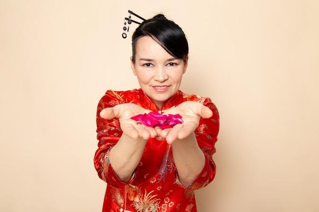 Eine vorderansicht schöne japanische geisha im traditionellen roten japanischen kleid mit haarstäbchen, die das elegante lächeln der roten rosenblätter auf der cremefarbenen hintergrundzeremonie japan ost posierend halten
