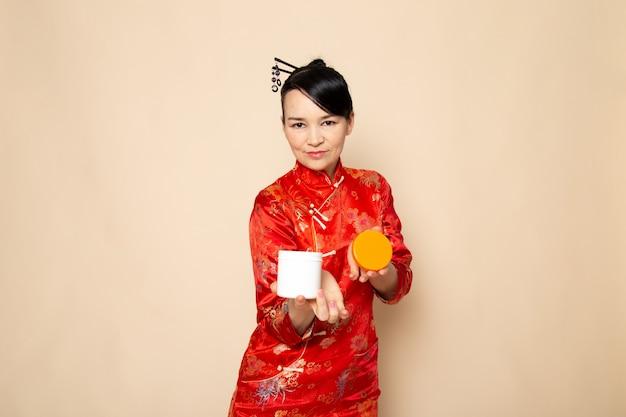 Eine vorderansicht schöne japanische geisha im traditionellen roten japanischen kleid mit haarstäbchen, die eröffnungscreme aufstellen, kann auf der cremehintergrundzeremonie japan riechen