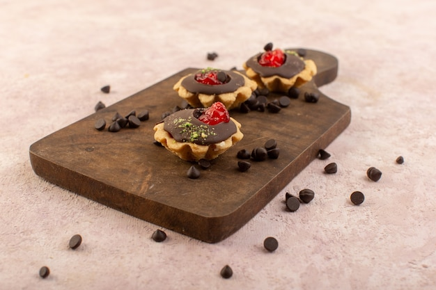 Eine vorderansicht schokoladenkuchen lecker auf dem hölzernen schreibtischzuckersüßfarbkuchen