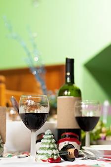 Eine vorderansicht von ein paar weinbechern auf dem tisch mit einer flasche und dem weihnachtsessen