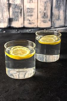Eine vorderansicht wasser mit zitrone frisches kühles getränk mit geschnittenen zitronen in transparenten gläsern auf der dunkelheit