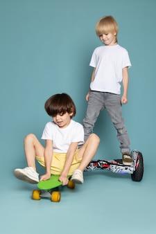 Eine vorderansicht zwei jungen entzückende süße süße glückliche roller roller und segway auf dem blauen boden