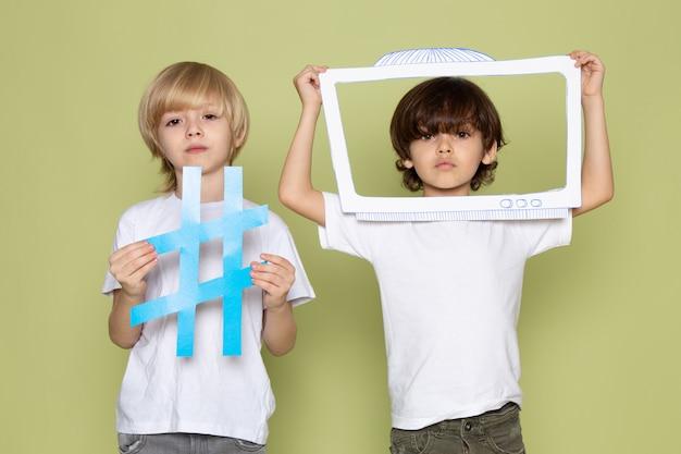 Eine vorderansicht zwei jungen in weißen t-shirts, die zeichen auf dem steinfarbenen raum halten