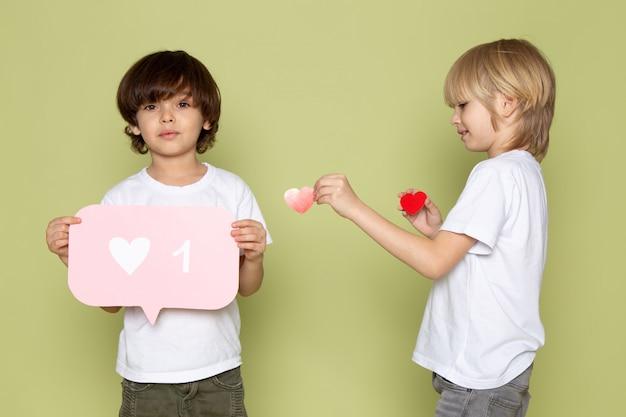 Eine vorderansicht zweier jungen, die in weißen t-shirts auf dem steinfarbenen raum entzückend sind