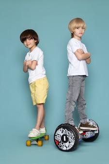Eine vorderansicht zweier jungen, die skateboards und segway in weißen t-shirts auf dem blauen boden reiten