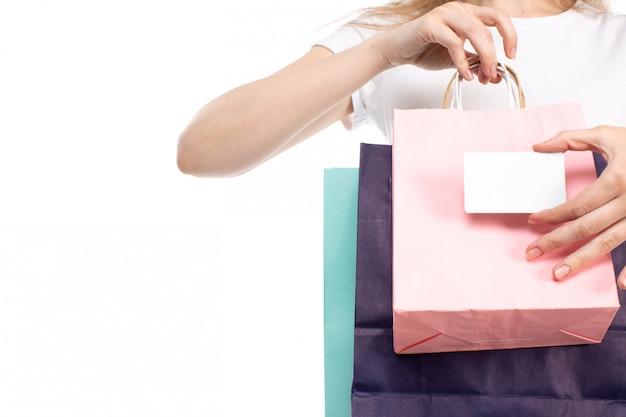 Eine vorderansichtfrau, die verschiedenfarbige einkaufspakete und weiße karte auf dem weiß hält